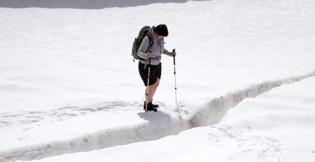 Bergsteigerin prüft den Übergang einer Gletscherspalte