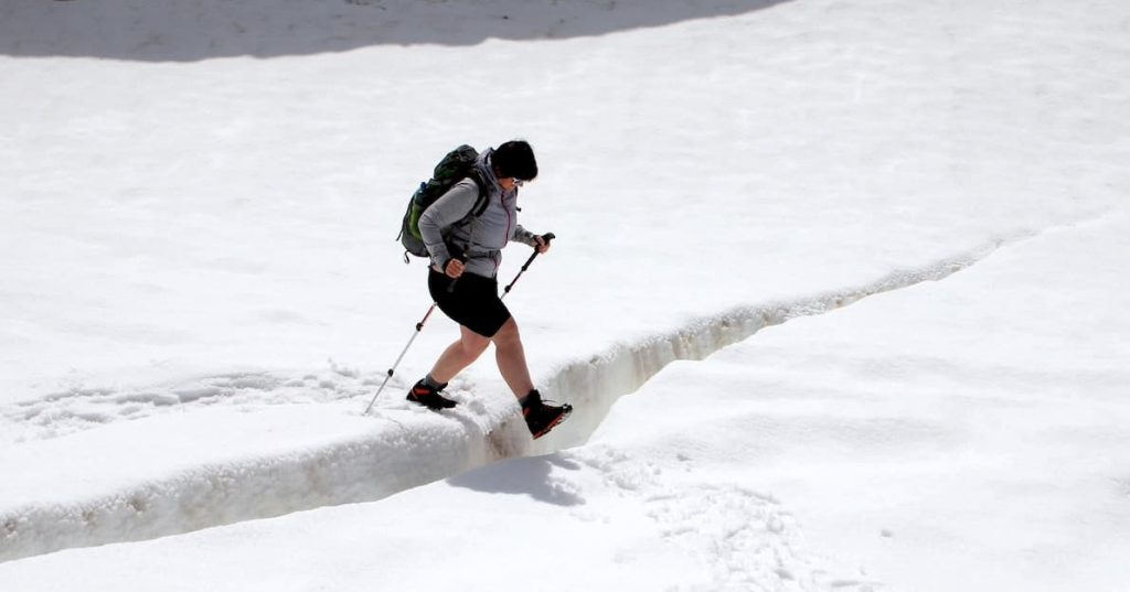 Bergsteigerin beim Übergang über eine Gletscherspalte